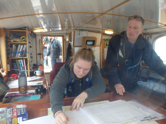 Andrew teaches a crew member to fill in Prolific's logbook